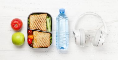 Healthy lunch box with sandwich and vegetables on wooden table. Top view. Flat lay