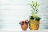 Ripe pineapple and coconut with sunglasses and headphones. Travel and vacation concept. With copy space