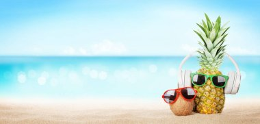 Summer tropical sea with sparkling waves, pineapple with sunglasses and headphones on hot sand beach. Travel and vacation concept with copy space