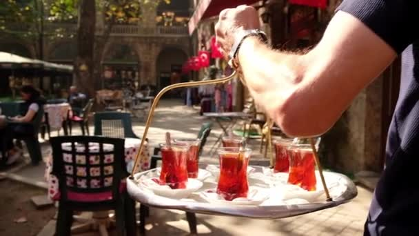 Waiter delivering traditional Turkish tea on a tray