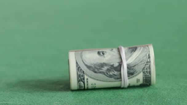 Rolle von Hundert-Dollar-Scheinen auf dem grünen Tisch