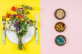 Fotografie Flat lay of wild flower bouquet on white plate and herbal capsules. Clean eating, paleo, biohacking, herbal medicine concept