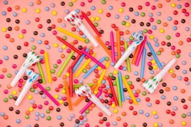 Colorful sprinkles, blowers and birthday candles on pink background, flat lay, top view