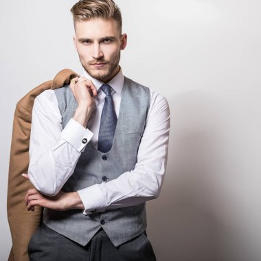 Elegant young handsome man with long stylish coat in hand.