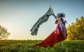 Fotografie Pohádka žena na chůdách s stříbrným vlajka ve světlé fantasy stylizaci. Venkovní fotografie výtvarného umění