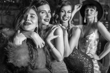Group of young laughing stylish girls dressed classical style in interior of luxury club.