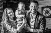 Fotografie Junge glückliche Familie zusammen im Inneren des Holzhauses. Schwarz-weiß-Porträt