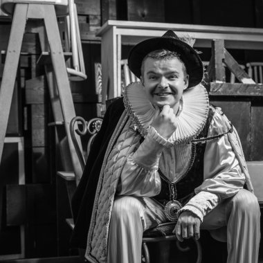 Actor dressed historical costume in interior of old theater. Black-white photo.
