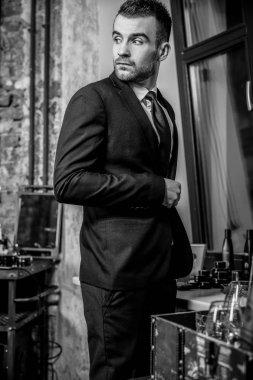 Elegant young man in barbershop. Black-white photo.