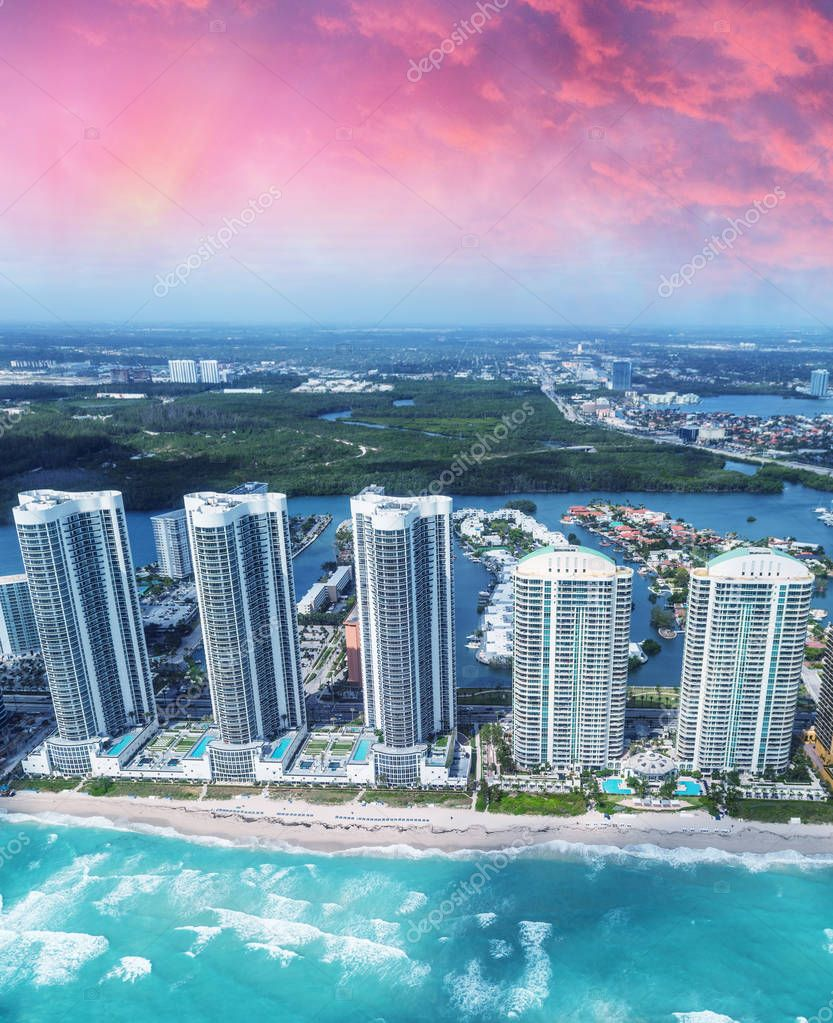 Helicopter view of North Miami Beach skyscrapers with sun and clouds.