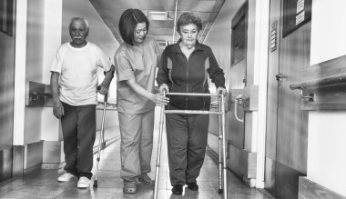Asian doctor helping elder woman with walker and man in hospital aisle.