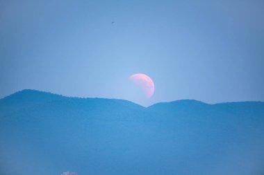 Lunar Eclipse, Moon rising behind a mountain.
