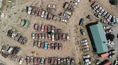 Overhead view of old cars gathered in a countryside parking.