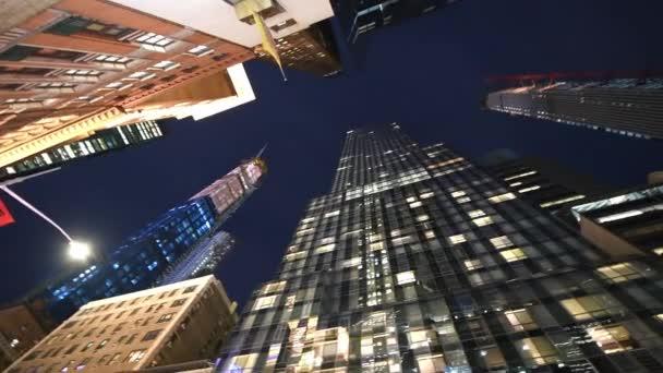 New York City - prosinec 2018: Street view vysokých mrakodrapů v noci, k obloze perspektivy. Město láká turisty 50 milionů ročně
