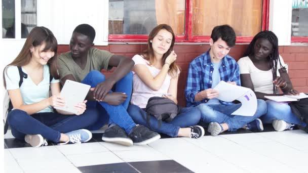 Skupina pěti multietnických teenagerů sedících na chodbě a pracujících s učebnicemi. Zpomalený pohyb
