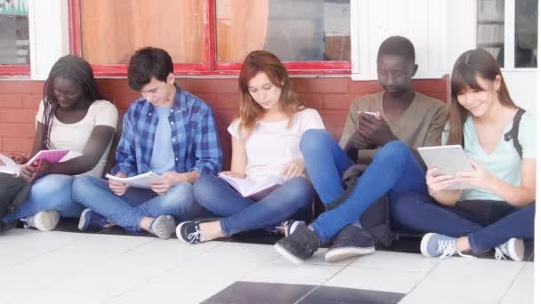 Skupina multietnických teenagerů sedících ve škole na hodině. Návrat do školy
