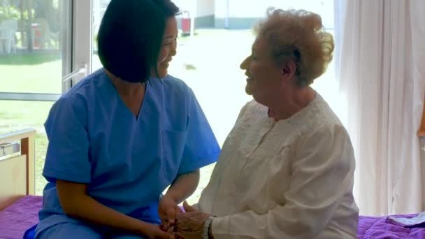 Sestra pomáhá starší žena sedí na její nemocniční posteli