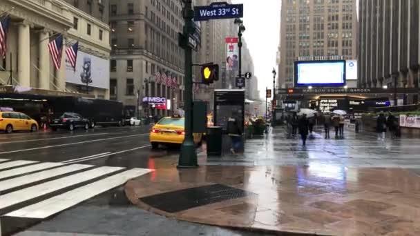 NEW YORK CITY - Prosinec 2018: Doprava a lidé na hlavní třídě za deštivého dne, jak je vidět z pohybující se kamery