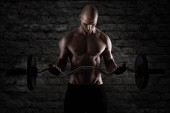 Fotografie Athletic man training biceps at the gym
