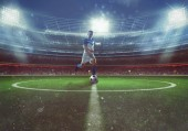 Soccer player hits the ball from the midfield at the stadium