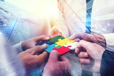 Business people join puzzle pieces in office. Concept of teamwork and partnership. double exposure with light effects