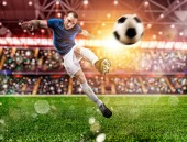 Football scene at night match with player kicking the ball with power.