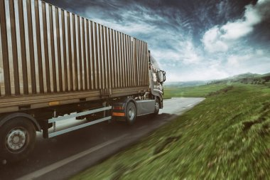 Grey truck moving fast on the road in a natural landscape with cloudy sky