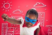 Dítě se chová jako superhrdina, aby zachránil svět na červeném pozadí