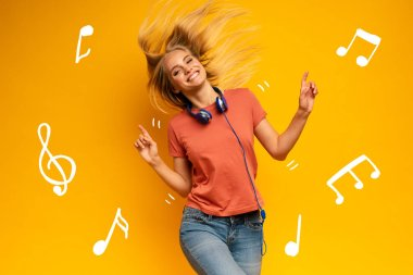 Blonde girl listens to music with headset. Joyful expression on yellow background