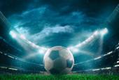 Egy focilabda közelsége a stadion közepén, amit a fényszórók világítanak meg.