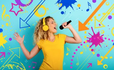 Girl with headset listens to music and song with microphone. emotional and energetic expression. Cyan background