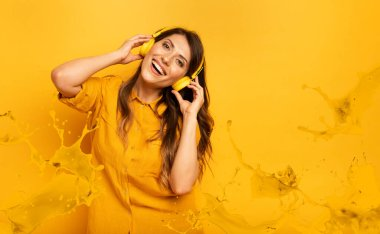 Girl with yellow headset listens to music and dances. emotional and energetic expression