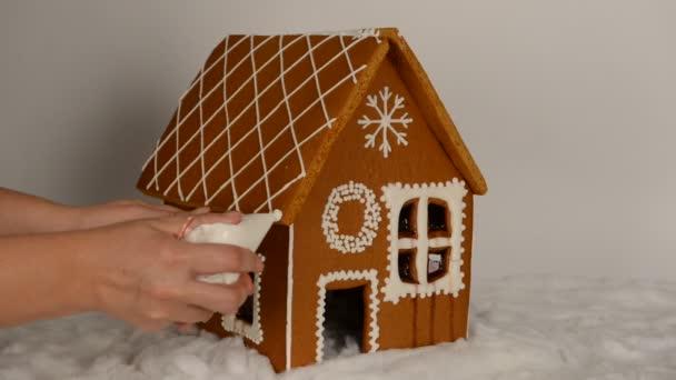 A kézzel készített ehető mézeskalács ház, hozzátéve, kézzel jegesedés a tető és a hó dekoráció