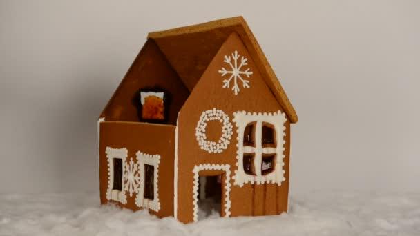 A kézzel készített ehető mézeskalács ház, hozzátéve, kézzel része a tető és a hó dekoráció