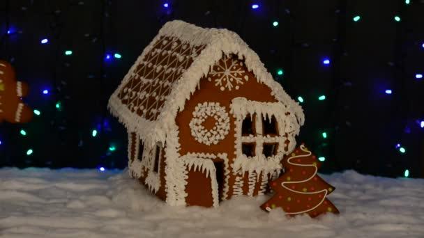 A kézzel készített ehető mézeskalács ház, hozzátéve kézzel kis ember, új év fa, hó dekoráció, girland háttér megvilágítás