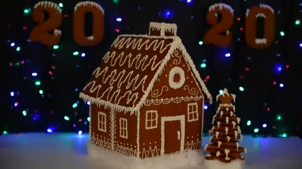 A kézzel készített ehető mézeskalács ház, újévi fa, 2020 felirat, hó dekoráció, girland háttér megvilágítás
