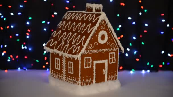 A kézi ehető mézeskalács ház, hó dekoráció, girland háttér megvilágítás