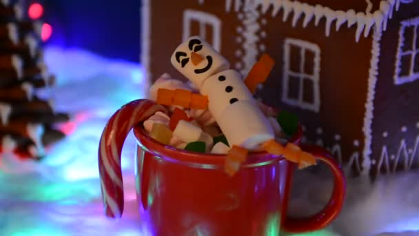 A boldog Marshmallow hóember a mag, kézi készítésű ehető mézeskalács ház, hó dekoráció, girland hó és a háttér megvilágítás