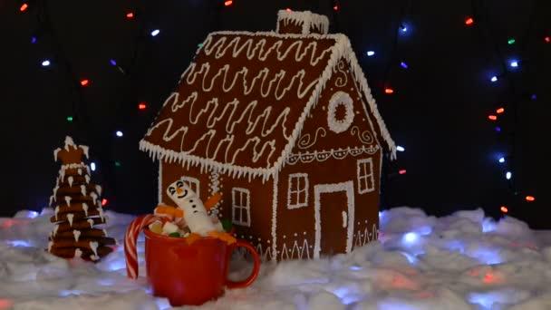 A kézzel készített ehető mézeskalács ház, fehérmályás hóember a mag, újév fa, hó dekoráció, girland hó és a háttér megvilágítás