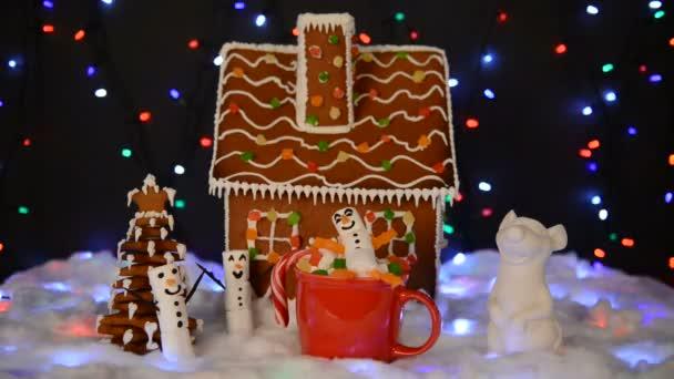 A kézi ehető mézeskalács ház, fehérmályás hóember a mag, egér-jelképe év 2020, új év fa, hó dekoráció, girland hó és a háttér megvilágítás