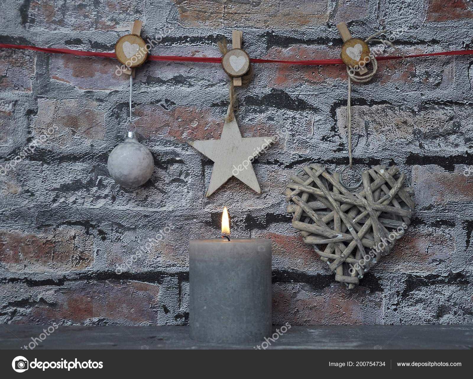 Burning Candle And Christmas Decoration In Front Of Brick Wall