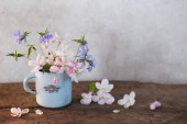 Fotografie jarní květiny v poháru na dřevěný stůl