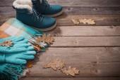 Fotografia Scarpe invernali, guanti, sciarpe su fondo in legno vecchio