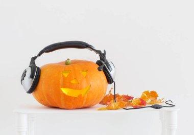 orange Halloween pumpkin with headphones on white background