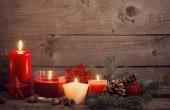 Weihnachtsdekoration mit roten Kerzen auf Holzgrund