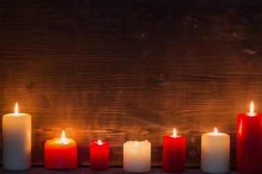 Burning candle on old dark wooden background