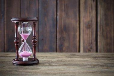 hourglass on dark wooden background