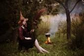 fiatal boszorkány az éjszakai erdőben tűz
