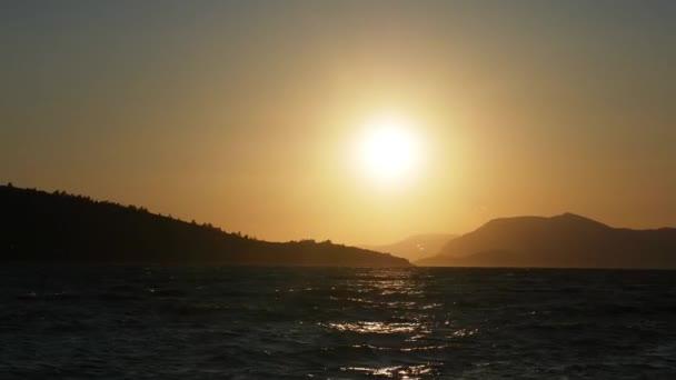 Stone beach, sun path, silhouettes of Islands, sunset