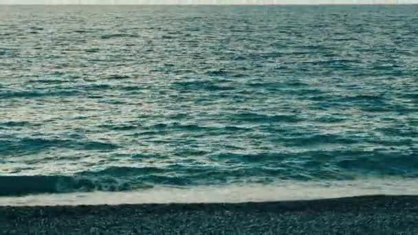 Pláž pestrobarevným kulaté oblázky a šplouchání vln, Slaný.